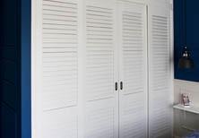 Гардеробная с дверями-жалюзи из крашеного дерева на рельсах